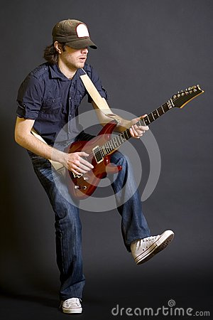 Guitarist playing his guitar with one leg up