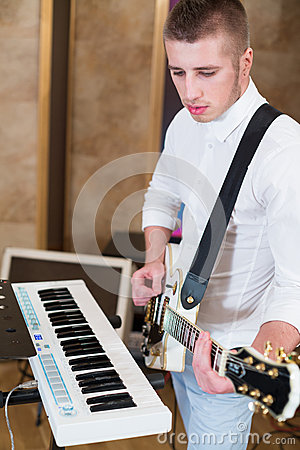 Guitarist  in the studio playing guitar next to the keyboards