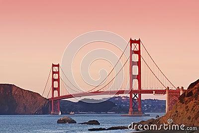 Guld- portbro på solnedgången