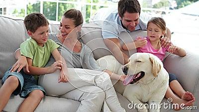 Gullig familj som tillsammans kopplar av på soffan med deras hund