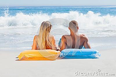 Gulliga par i baddräkten som tillsammans solbadar