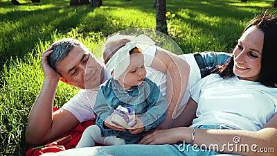 Gulligt behandla som ett barn flickan som rymmer hennes sko, och föräldrar som ligger bredvid henne på gräs parkerar in stock video