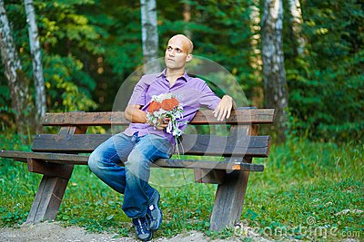 Guy with bouquet waiting for his girlfriend outsid