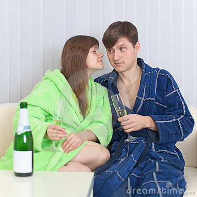 Guy and girl drink champagne wine on a sofa