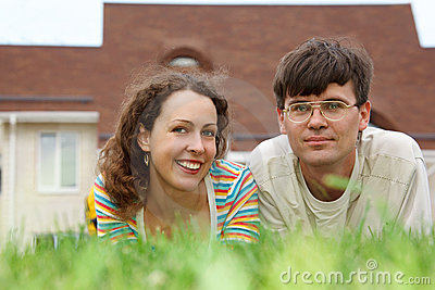 Guy with girl lying on lawn in front of new home