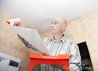 Guy glues ceiling the tile