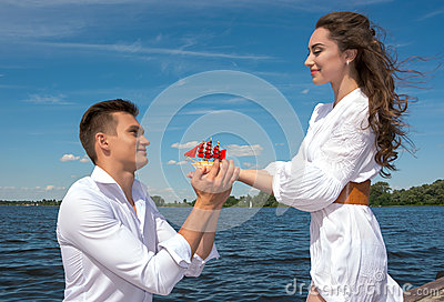 The guy is on his knees before the girl on a wooden pier near th
