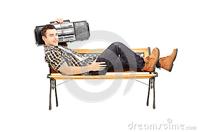 Guy holding a boombox on his shoulder and lying on a bench