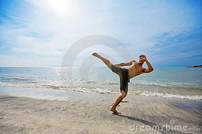 Guy kick boxing by the beach