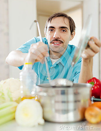Guy with ladle cooking vegetables soup at kitchen