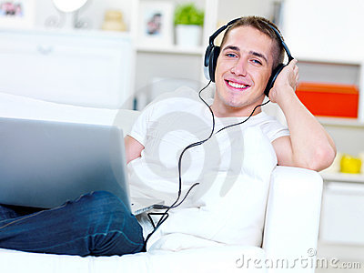 Guy listening music in headphone from laptop