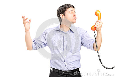 A guy in love holding a telephone tube and giving kisses