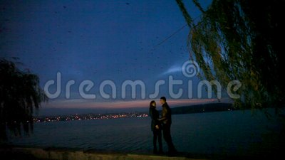 Guy lovingly embraces and kisses a girl against the backdrop of a night city. The couple walks along the night embankment against the backdrop of a lake, lights stock video footage