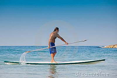 The guy with an oar on a surfboard.