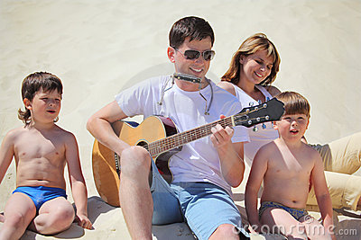 Guy plays guitar and lip accordion with children
