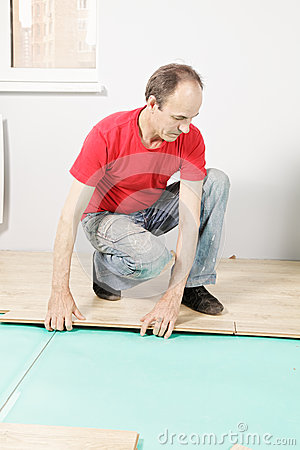 Guy in red installing flooring