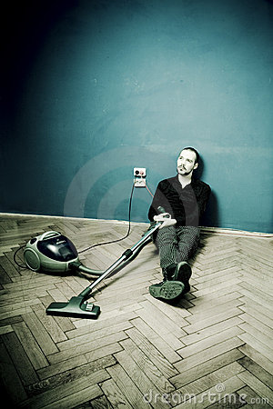 Guy rests on floor with vacuum