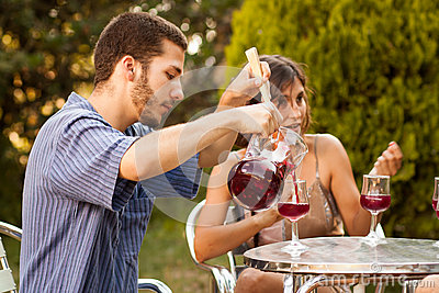 Guy serving sangria with friends in a terrace