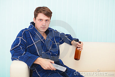 Guy sits on sofa and drinks beer looking TV