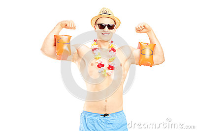 Guy in a swimsuit with swimming arm bands showing his muscles