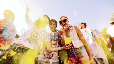 A guy throws yellow powder in the air at holi colour festival in slow motion. A guy and two of his other friends throw yellow powder into the air at holi colour