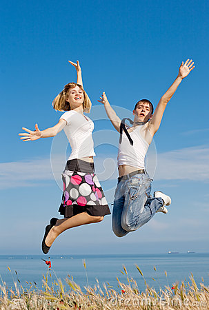 Guy in tie and slim girl jumping