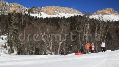 Adults and children ride on the snow slope. stock video