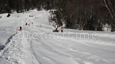 Adults and children ride on the snow slope. stock video footage