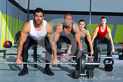 Gym group with weight lifting bar crossfit workout