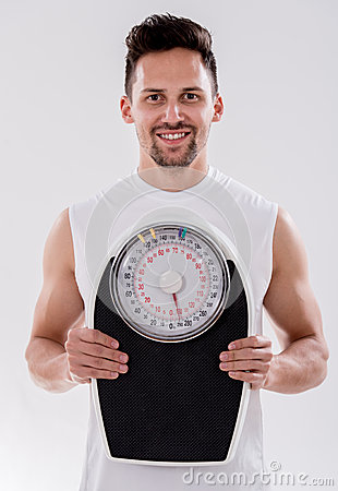 Gym man with a weight scale