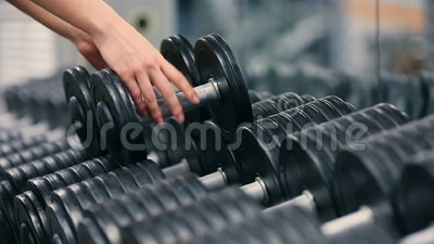 Gym woman strength training lifting dumbbell weights getting ready for exercise workout. Female fitness girl exercising. Indoor in fitness center. Stoke stock footage