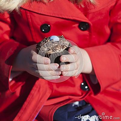 Mädchen, das Brötchen oder Kuchen hält