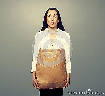 Häpen ung kvinna som rymmer den pappers- påsen