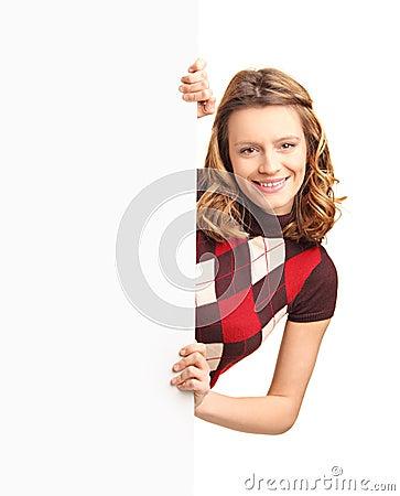 Härlig flicka som poserar bak en vit panel