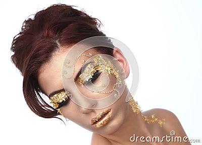Härlig kvinna som smyckas med bladguldskönhetsmedel