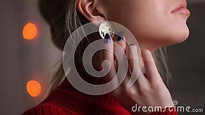 Härlig modell för mode i den röda klänningen som poserar trycka på örhängen
