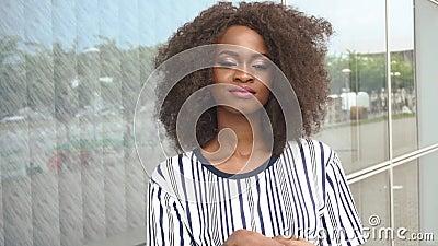 Härlig sexig sinnlig ung afrikansk amerikankvinna som ler charmingly på glasväggbakgrundsnärbilden stock video