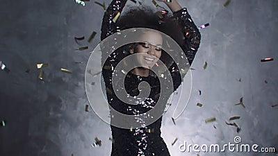 Härlig svart kvinna som kastar guld- konfettier, ultrarapid