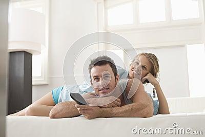 Hållande ögonen på TV för lyckliga par hemma