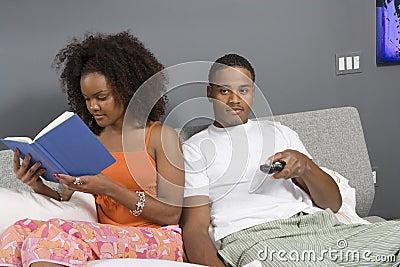 Hållande ögonen på TV för man medan läs- roman för kvinna