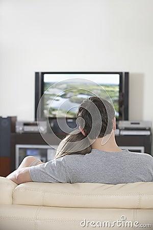 Hållande ögonen på TV för par tillsammans hemma