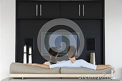Hållande ögonen på TV för par tillsammans i vardagsrum