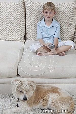 Hållande ögonen på TV för pojke med hunden