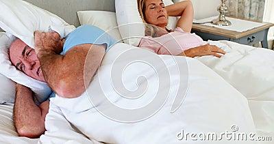Hög man som ligger på säng och beläggning hans öron med kudden arkivfilmer