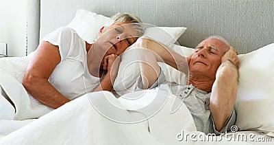 Hög man som täcker hans öron medan kvinna som snarkar i sovrum arkivfilmer
