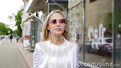 Hübsche Blondine in der stilvollen Ausstattung gehend hinunter die Straße in der Zeitlupe stock footage