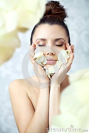 Hübsche Brunetteholdingblumenblätter nah an Gesicht