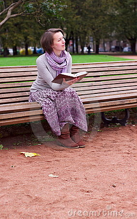 Hübsche Frau, die ein Buch auf Bank und dem Denken liest