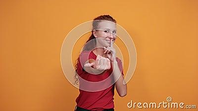 Hübsche junge Dame in rotem Hemd lädt jemanden ein, der den Finger am Kinn hält stock footage