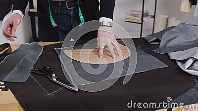 Hübscher Schneider, der in seinem Studio, zeichnende Schablone auf Gewebe arbeitet Kreativ eine Arbeit des Schneiders, den Zeichn stock video footage